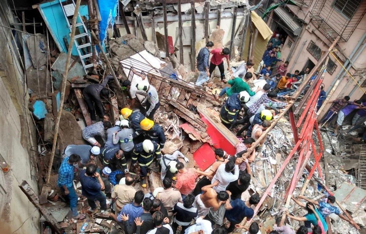 Lực lượng cứu hộ tìm kiếm nạn nhân bị mắc kẹt dưới đống đổ nát của tòa nhà bị sập ở Mumbai, Ấn Độ ngày 16/7. (Ảnh: India Today/TTXVN)