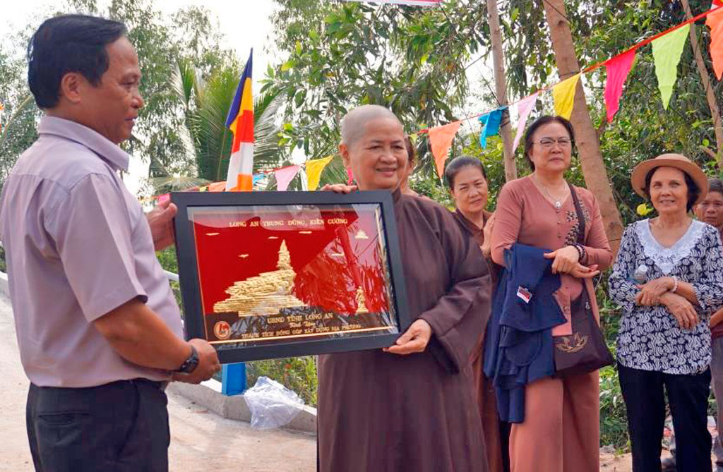 Deputy Secretary of Party Committee of Tan Thanh commune - Ho Phuoc Hung awarded certificates of merit and souvenirs of Long An provincial People's Committee to the representative of Bao Quang Pagoda