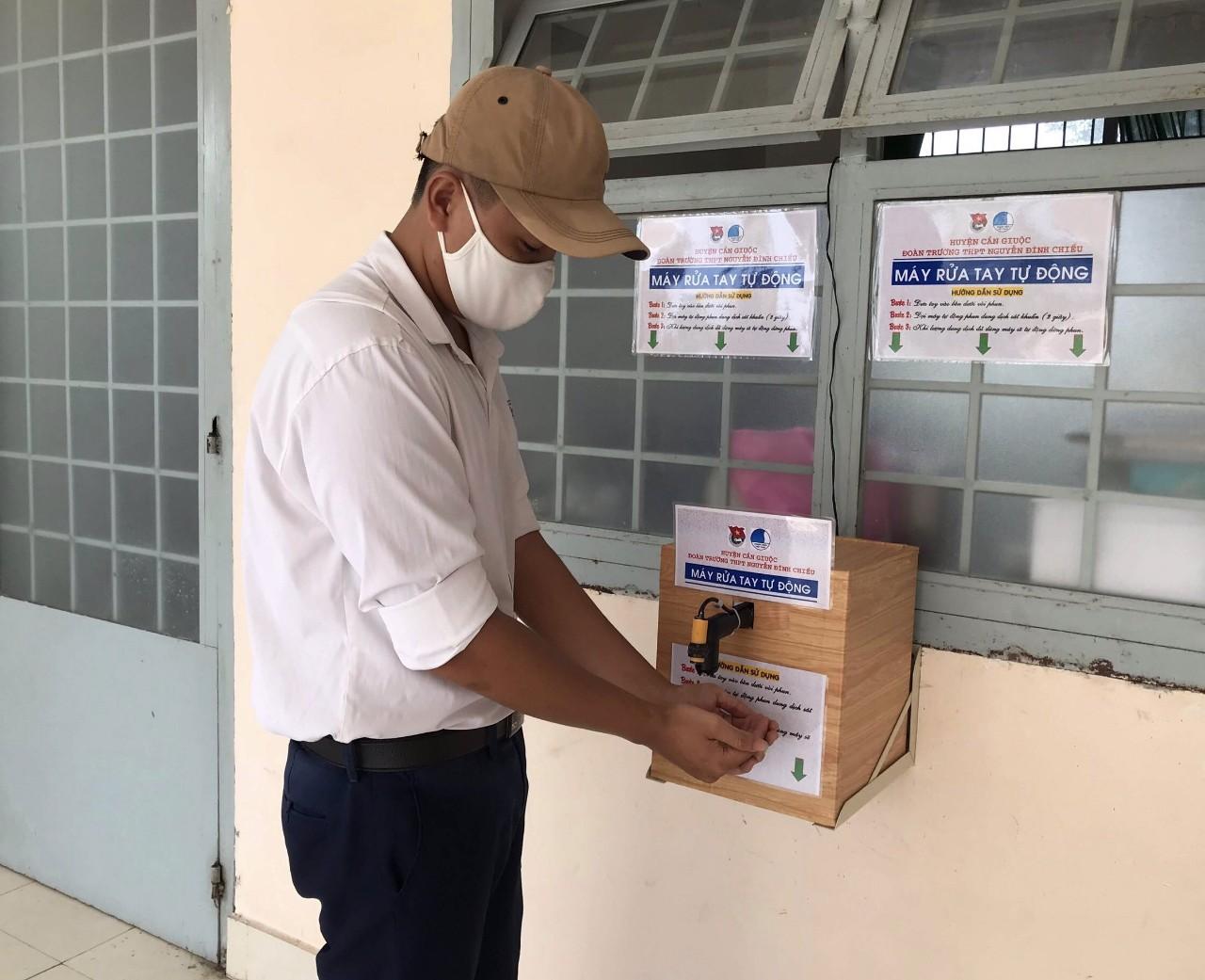 Học sinh Trường THPT Nguyễn Đình Chiểu sử dụng máy rửa tay sát khuẩn tự động