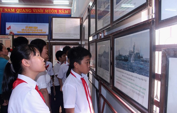Học sinh tham quan một triển lãm ảnh. (Ảnh: Hồng Hiếu/TTXVN)