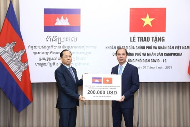 Vietnamese Deputy Minister of Foreign Affairs Nguyen Quoc Dung (R) presents the token of the aid worth 200,000 USD to Cambodian Ambassador to Vietnam Chay Navuth. (Photo: VNA)