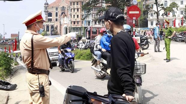 Công an huyện Tam Đảo xử lý trường hợp chủ phương tiện không đội mũ bảo hiểm khi tham gia giao thông. (Ảnh: Hoàng Hùng/TTXVN)