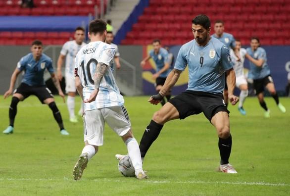 Messi với pha đi bóng vượt qua tiền đạo Luis Suarez (Uruguay). (Nguồn: Reuters)