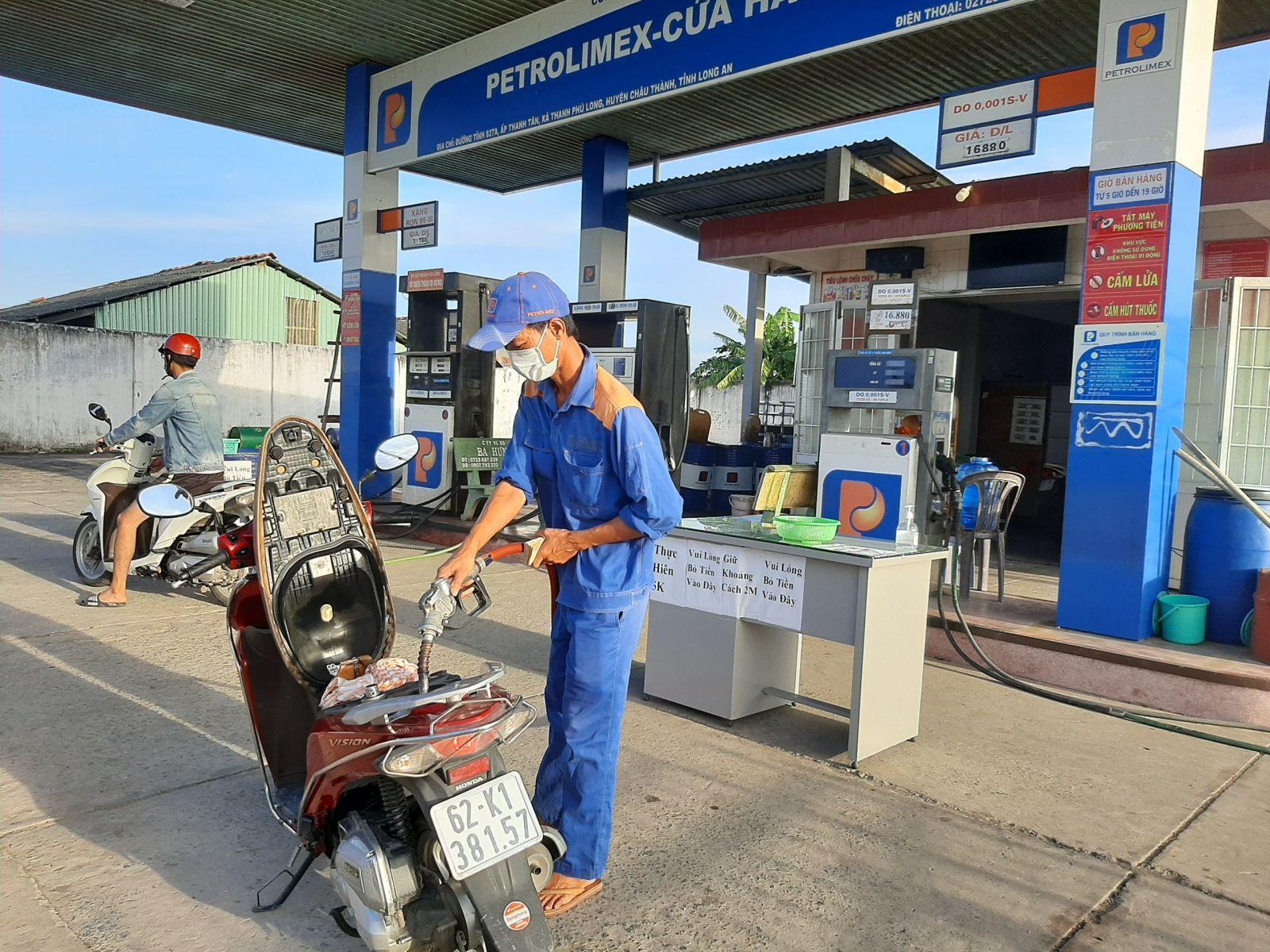 Sau khi mở nắp bình xăng xe, khách hàng đứng lùi lại 2m trong lúc nhân viên đang đổ xăng