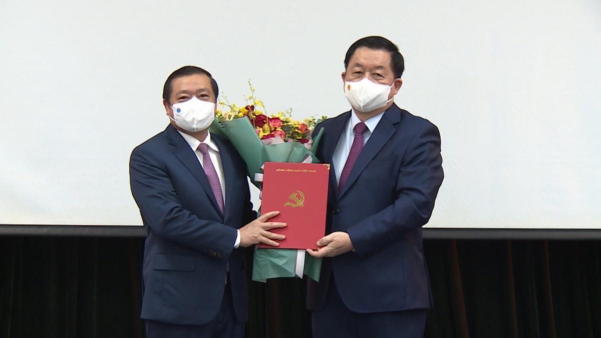 Ông Nguyễn Trọng Nghĩa trao quyết định và tặng hoa chúc mừng ông Lại Xuân Môn.
