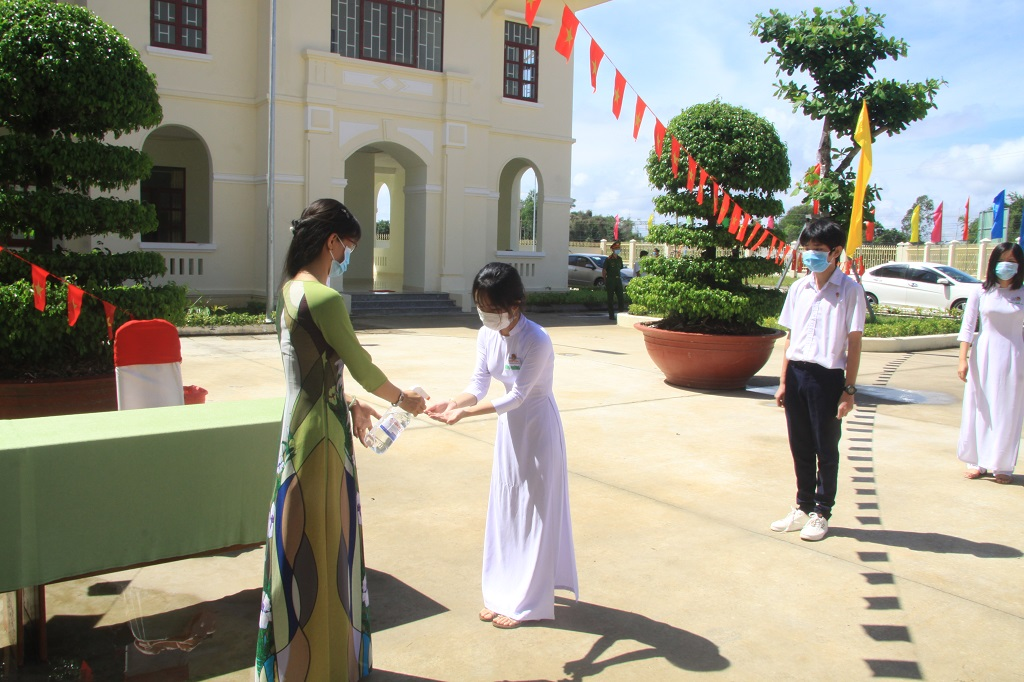 Students are disinfected hands and measured body temperature before entering the ceremony ground