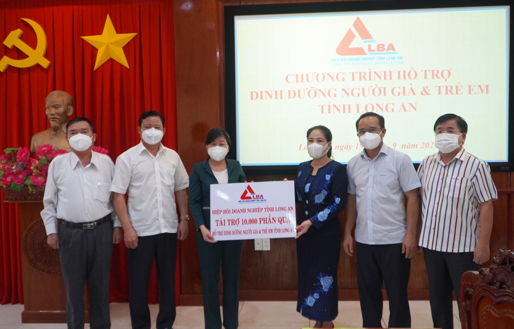 Standing Vice Chairwomam of the Provincial Business Association - Ninh Thi Bich Thuy (3rd, R) presents a symbolic board to support 10,000 gifts to Long An province